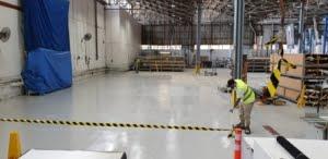 Applicators of Epoxy Flooring Brisbane spreading epoxy paint on industrial warehouse